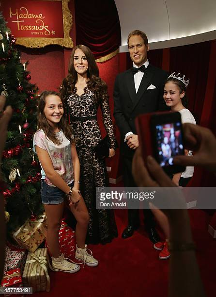 People pose and take photos on their mobile phones of themselves posing alongside wax figures of Princess Catherine and Prince William at Maddam...