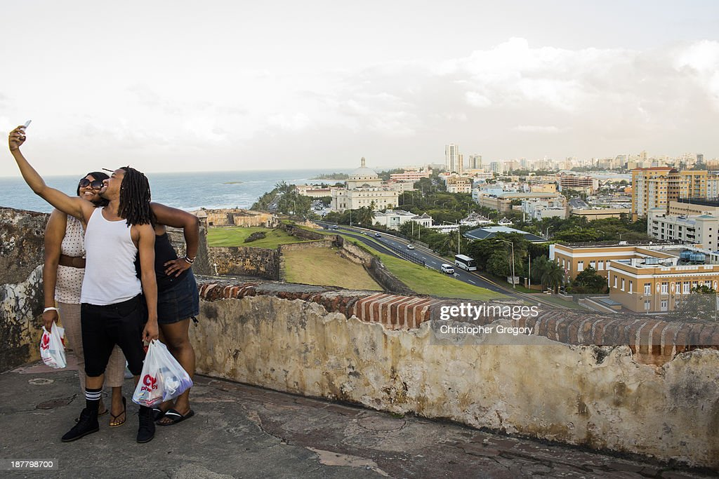 People pose for a photo in front of Old San Juan, the center for Puerto Rican tourism, on November 12, 2013 in San Juan, Puerto Rico. The island territory of the United States, Puerto Rico, is on the brink of a debt crisis as lending has skyrocketed in the last decade as the government has been issuing municipal bonds. Market analysts have rated those bonds as junk and suspect it's 70 billion dollar debt might be unserviceable in the near future. With no industry other than tourism and the recent collapse of the real estate market, the way out is unclear.