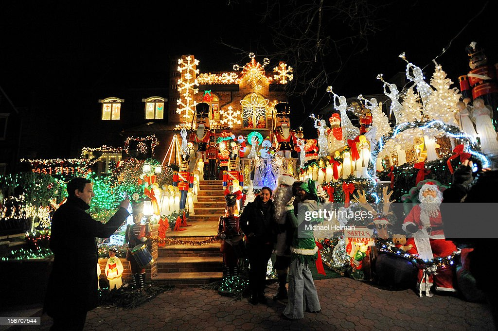 People pose for a photo with a man dressed as Santa Claus in front of a decorated house on Christmas Eve December 24, 2012 in the Dyker Heights neighborhood of the Brooklyn borough of New York City. The neighborhood in the south part of the borough, is known for its yearly display of over the top holiday themed decorations.