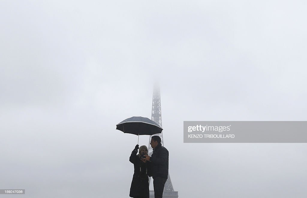 People pose for a photograph at the Trocadero square, with a view of the Eiffel tower in the background, on January 10, 2013, in Paris. AFP PHOTO / KENZO TRIBOUILLARD