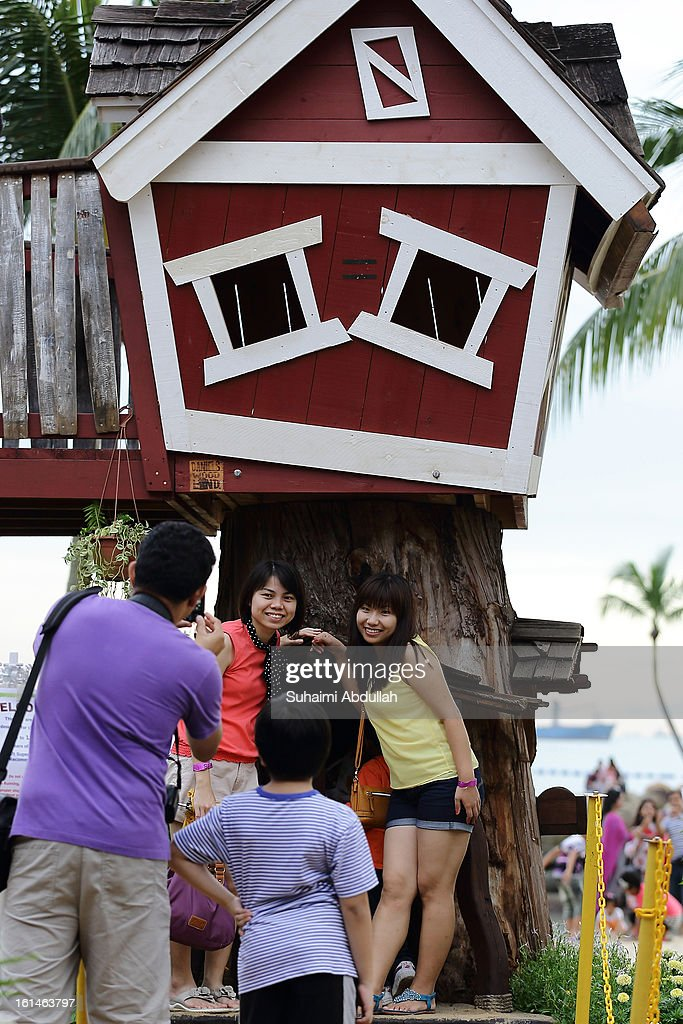 People pose for a photograph in front of a tree house at the Sentosa Flowers exhibition at Palawan Beach on February 11, 2013 in Singapore. Millions of spring flowers decorate the island in celebration of the Chinese New Year, the year of the Snake.