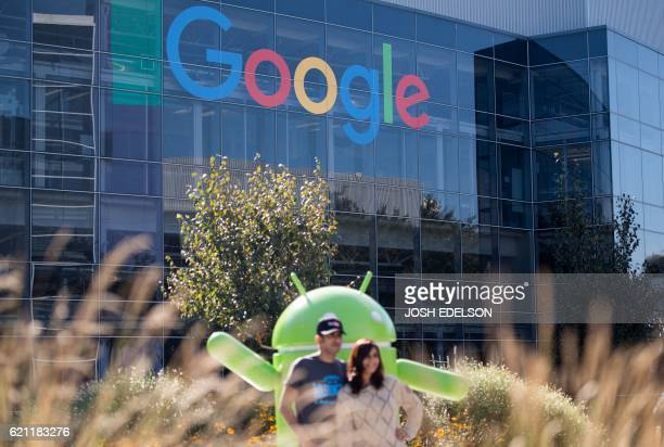 People pose for a picture near a Google sign and Android statue at the Googleplex in Menlo Park California on November 4 2016 / AFP PHOTO / JOSH...