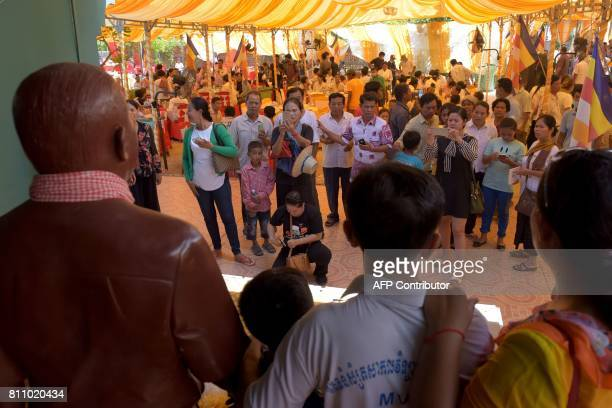 People pose for a picture with a statue of Cambodian critic Kem Ley during the first anniversary of his murder at his mother's home in Takeo province...