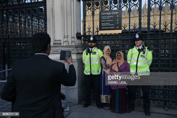 TOPSHOT People pose for a picture with police officers outside the Houses of Parliament in central London on March 26 2017 The British government...