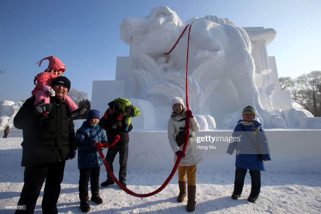 People pose for photograph beside a large snow sculpture of dinosaur at the 26th Harbin International Snow Sculpture Art Expo in Sun Island park on December 22, 2013 in Harbin, China. The Harbin International Ice and Snow Sculpture Festival is one of the largest ice and snow festivals in the world and is a popular winter destination for both Chinese and foreign visitors.