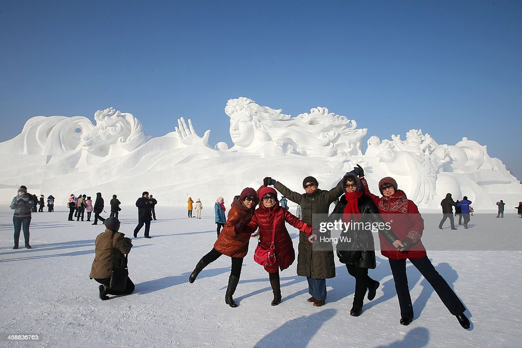 People pose for photograph beside a large snow sculpture with the 117-meter-long and 26-meter-high at the 26th Harbin International Snow Sculpture Art Expo in Sun Island park on December 22, 2013 in Harbin, China. The Harbin International Ice and Snow Sculpture Festival is one of the largest ice and snow festivals in the world and is a popular winter destination for both Chinese and foreign visitors.