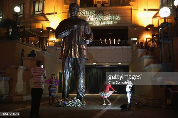 People pose for photographs and children dance at the base of a 20foottall statue of former South African President Nelson Mandela in Mandela Square...