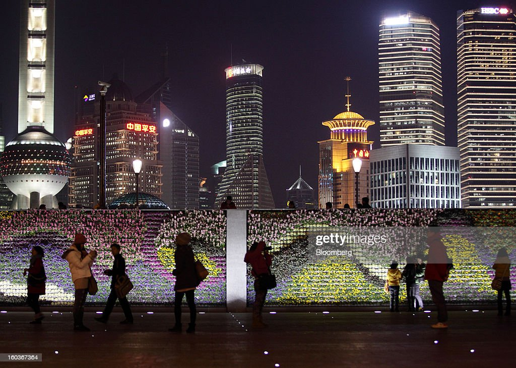 People pose for photographs and walk along the Bund as commercial buildings stand in the Pudong area at night in Shanghai, China, on Monday, Jan. 28, 2013. China's economic growth accelerated for the first time in two years as government efforts to revive demand drove a rebound in industrial output, retail sales and the housing market. Photographer: Tomohiro Ohsumi/Bloomberg via Getty Images