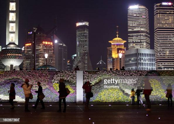 People pose for photographs and walk along the Bund as commercial buildings stand in the Pudong area at night in Shanghai China on Monday Jan 28 2013...