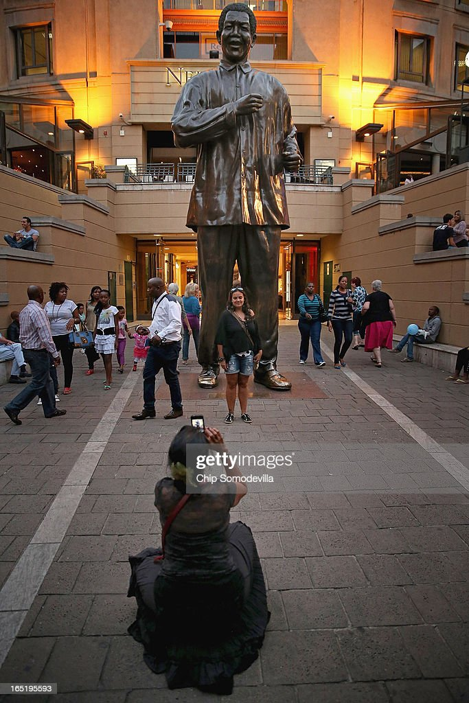 People pose for photographs in front of the 20-foot-tall statue of former South African President Nelson Mandela in the shopping square named after the anti-apartheid hero April 1, 2013 in Johannesburg, South Africa. Mandela, 94, is recovering from pneumonia in hospital, his third stay in the last four months. Mandela's lungs were damaged when he contracted tuberculosis during his 27 years in the infamous Robben Island prison. Mandela became the nation's first democratically elected president in 1994 following the end of apartheid.