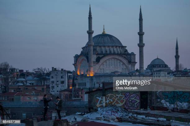 People pose for photographs on a rooftop of an old Istanbul Han overlooking the Bosphorus strait on March 18 2017 in Istanbul Turkey Turkey will hold...