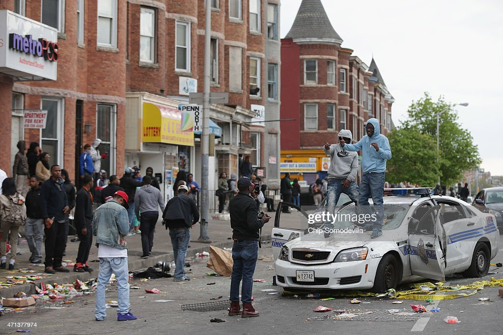 People pose for photographs on the hood of a Baltimore Police car destroyed by demonstrators sits in the street near the corner of Pennsylvania and...