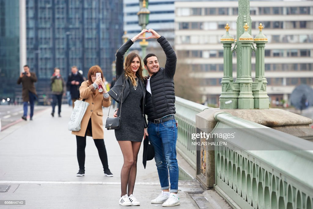 TOPSHOT - People pose for photographs on Westminster Bridge in central London on March 23, 2017 after the bridge reopened to traffic following its closure during the March 22 terror attack. Britain's parliament reopened on Thursday with a minute's silence in a gesture of defiance a day after an attacker sowed terror in the heart of Westminster, killing three people before being shot dead. Sombre-looking lawmakers in a packed House of Commons chamber bowed their heads and police officers also marked the silence standing outside the headquarters of London's Metropolitan Police nearby. N