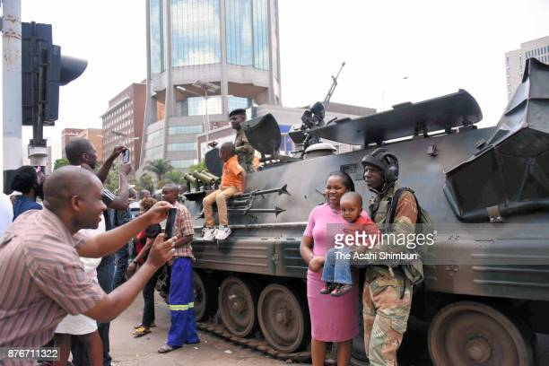 People pose for photographs with a soldier on November 19 2017 in Harre Zimbabwe