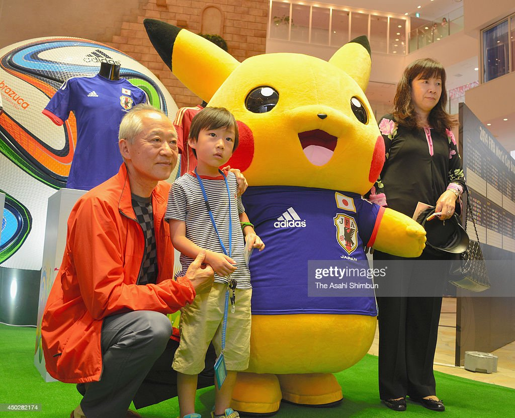 People pose for photographs with Pikachu wearing Japan national team uniform during a photo session at Hankyu Department Store Umeda branch on June 7, 2014 in Osaka, Japan.