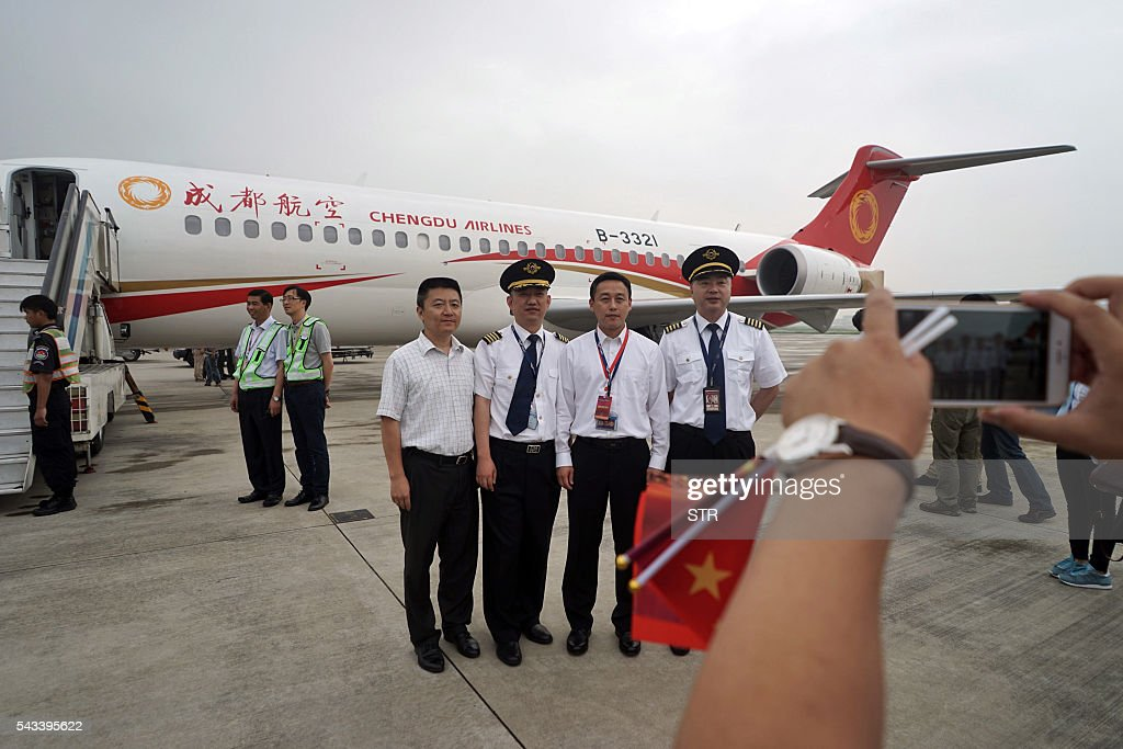People pose for photos after China's first domestic regional jet ARJ21-700 (behind) arrived at Shanghai Hongqiao Airport after making its first flight from Chengdu to Shanghai on June 28, 2016. China's homegrown regional jet made its first commercial flight on June 28, Chengdu Airlines said, after months of delays raised questions about the country's ambitious plans for domestically produced planes. / AFP / STR / China OUT