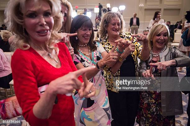 People pose for photos as polls close and results come in before republican presidential candidate Donald Trump speaks during a campaign press...
