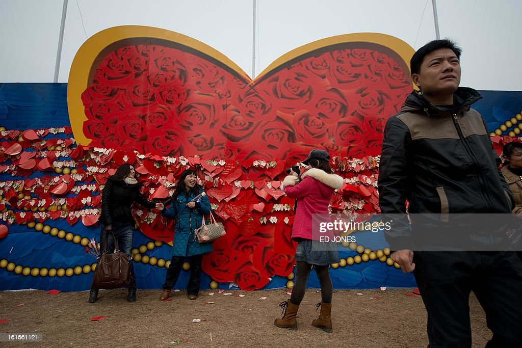 People pose for photos before a heart-shaped backdrop at a park in Beijing on Febraury 14, 2013. Businesses in the Chinese capital were said to be fearing the proximity of Chinese Lunar New Year falling just days before Valentine's day, after some nine million Beijingers were reported to have left the city for the annual holiday exodous, according to state media. AFP PHOTO / Ed Jones