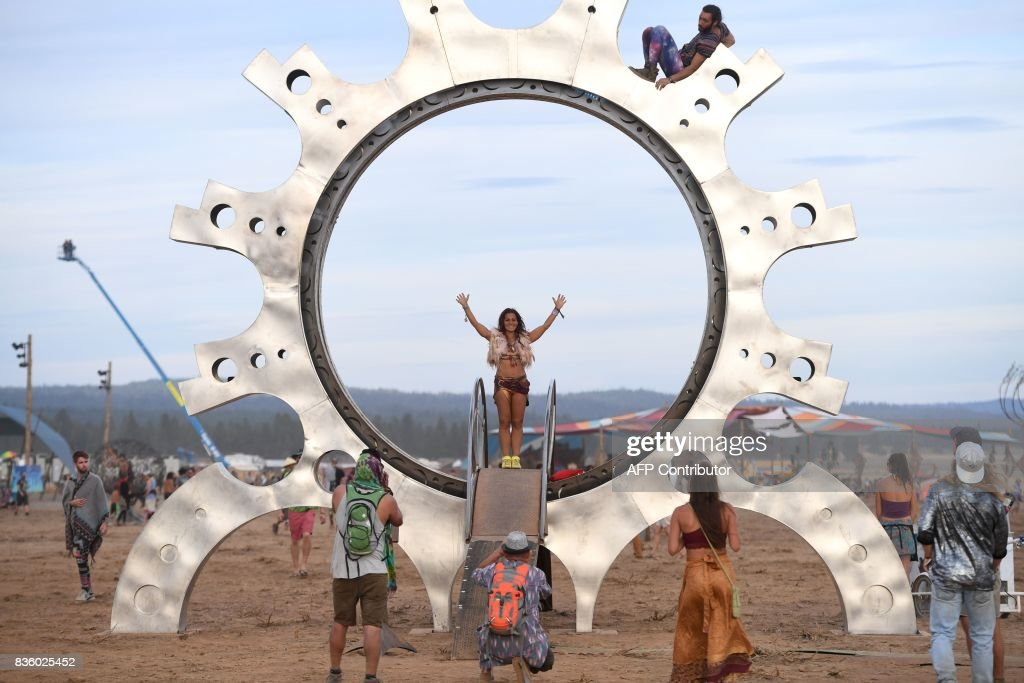 People pose for photos in an installation called Exsucitare Triectus by artist Orion Fredericks at the Oregon Eclipse Festival, August 20, 2017, at Big Summit Prairie ranch in Oregon's Ochoco National Forest near the city of Mitchell ahead of the total solar eclipse on August 21, 2017. / AFP PHOTO / Robyn Beck / RESTRICTED