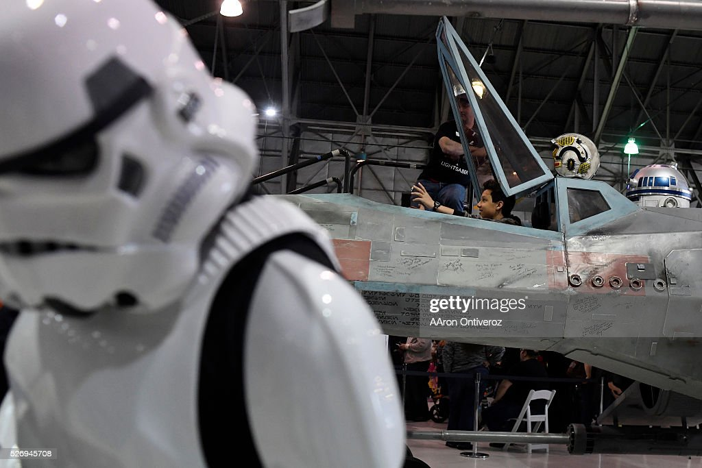 People pose for photos inside on an X-wing Starfighter during a Star Wars themed day at Wings Over the Rockies on Sunday, May 1, 2016.