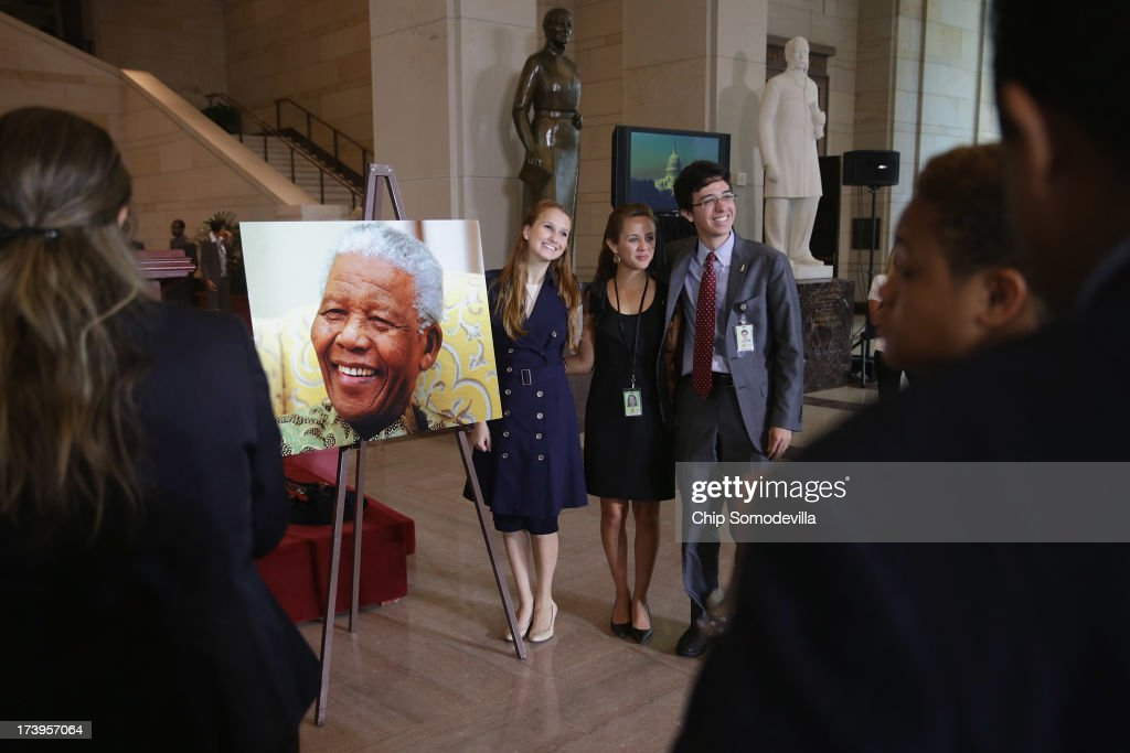 People pose for photos with an image of Nobel Peace Prize laureate and former South Africa President Nelson Mandela before a ceremony to celebrate Mandela on his 95th birthday in the U.S. Capitol Visitor Center July 18, 2013 in Washington, DC. July 18 is Nelson Mandela Day, during which people are asked to give 67 minutes of time to charity and service in their community to honor the 67 years Mandela gave to public service. Mandela was admitted to a South African hospital June 8 where he is being treated for a recurring lung infection.