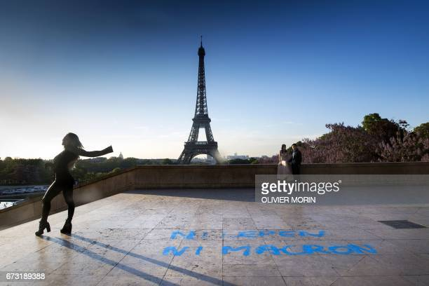 TOPSHOT People pose for pictures in front of the Eiffel Tower at the Trocadero plazza where a graffiti on the ground refering to the second round of...