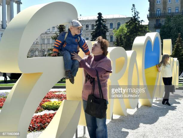 People pose for pictures in front of the official logo for the Eurovision Song Contest on Independence Square in Kiev on May 3 2017 The Eurovision...