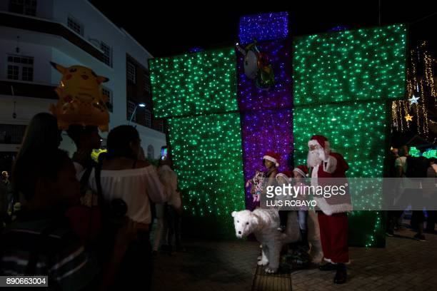 People pose for pictures next to Christmas decorations in Cali Colombia on December 11 2017 / AFP PHOTO / LUIS ROBAYO