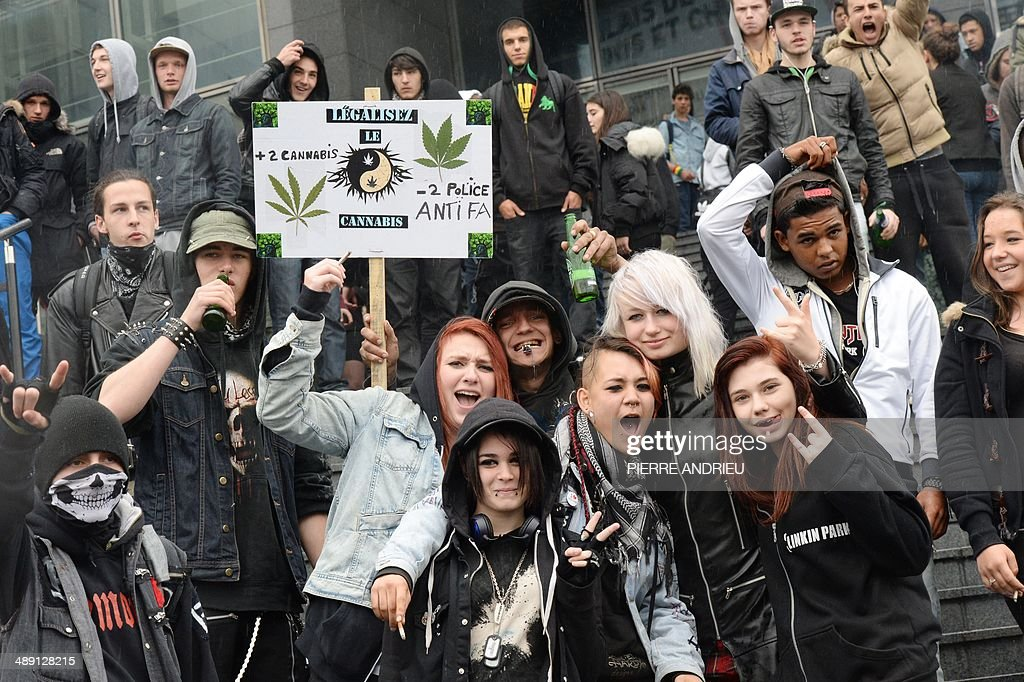 People pose in front a placard reading 'Legalize cannabis' as they take part in a protest to call for the legalization of marijuana on May 10, 2014 in Paris. About 147 million people globally -- or about 2.5 percent of the population -- use cannabis, according to the World Health Organization.
