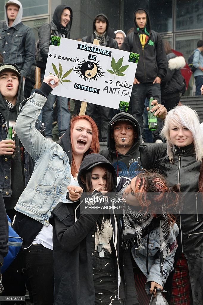 People pose in front a placard reading 'Legalize cannabis' as they take part in a protest to call for the legalization of marijuana on May 10, 2014 in Paris. About 147 million people globally -- or about 2.5 percent of the population -- use cannabis, according to the World Health Organization. AFP PHOTO / PIERRE ANDRIEU