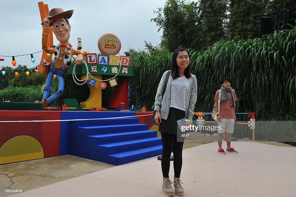 People pose in front of a model of Woody, one of the main characters in the Toy Story movie trilogy, at Toy Story Land at Hong Kong's Disneyland theme park on November 17, 2011. The attraction is the first stage of the resort's expansion.