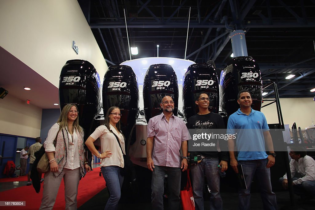 People pose in front of the five outdoor motors on a Cigarette boat at The Miami International Boat Show at the Miami Beach Convention Center on February 15, 2013 in Miami Beach, Florida. The boat show has more than 3,000 boats on display and more than 1,000 boating accessories, the show ends on Monday.