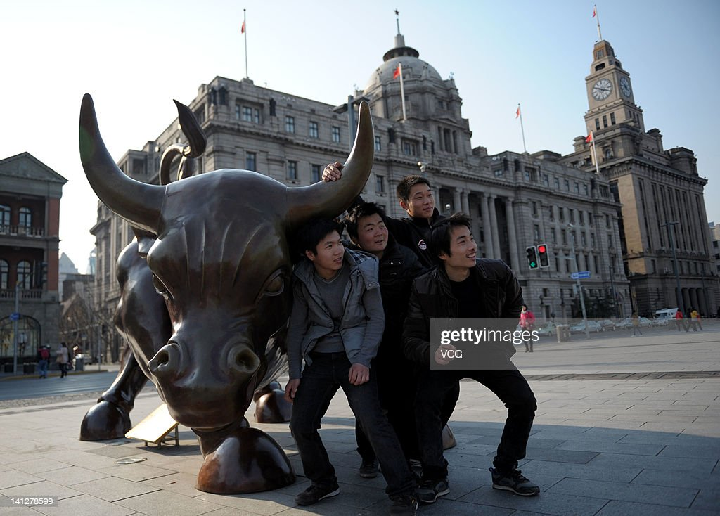 People pose with a bull sculpture at the Bund Financial Square on March 13, 2012 in Shanghai, China. Shanghai embraced a sunny day on Tuesday, as the cold wet weather has persisted for over a month.