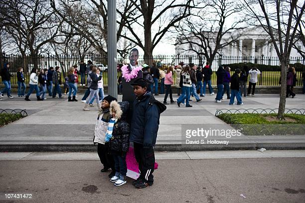 People pose with a cardboard standee of President in front of the White House in Washington DC on February 14 2009