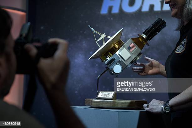 People pose with a model of the New Horizons probe at the Johns Hopkins University Applied Physics Laboratory July 14 2015 in Laurel Maryland The...