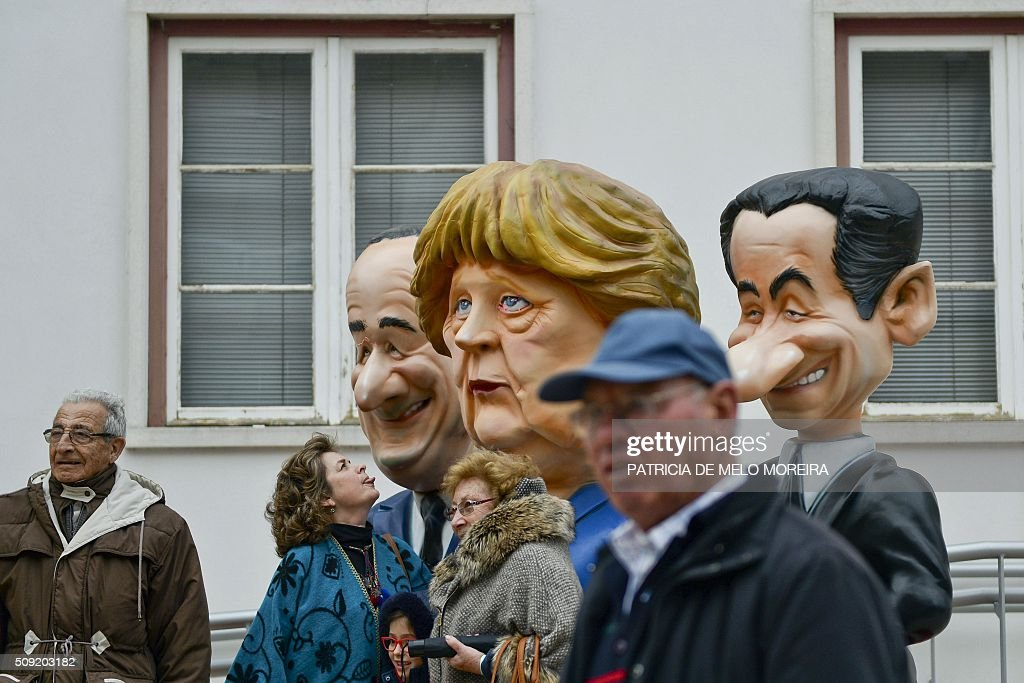 People pose with cartoon figures of French president Francois Hollande (L) German Chanceller Angela Merkel (C) and French former President Nicolas Sarkozy (R) during the annual parade in Torres Vedras on February 9, 2016. The Torres Vedras Carnival is allegedly the 'most Portuguese' of all the carnivals in the country recognized by the strong political and football satire of the revelers disguises and their floats. / AFP / PATRICIA DE MELO MOREIRA