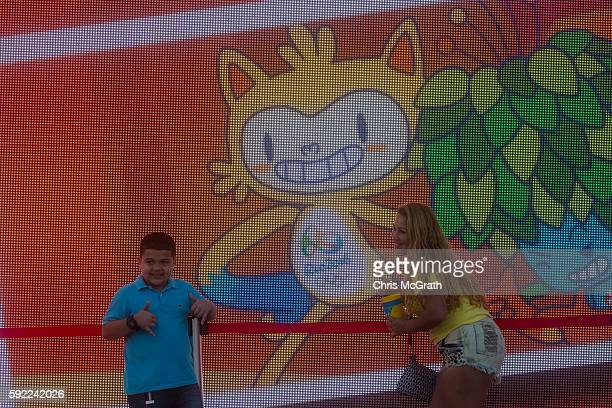 People pose with the Rio 2016 mascot 'Vinicius' in front of a screen at Olympic Park on Day 15 of the Rio 2016 Olympic Games on August 19 2016 in Rio...