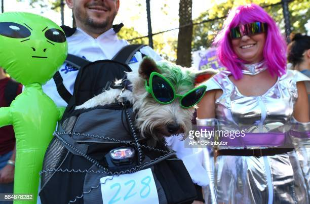 People pose with their dog in costume during the 27th Annual Tompkins Square Halloween Dog Parade in Tompkins Square Park in New York on October 21...