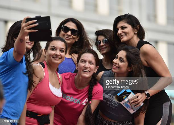 People poses for photograph after the perform different asanas during the International Yoga Day organized by Reebok and Ministry of AYUSH at...