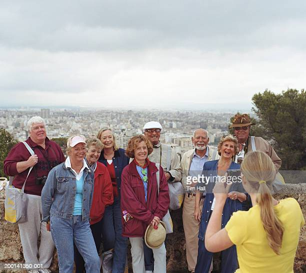 People posing for woman taking photograph, cityscape in background