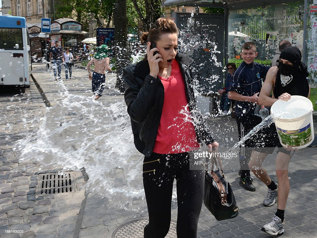 People pour water on a passer-by in the western Ukrainian city of Lviv on May 6, 2013, as they celebrate Clean Monday (or Wet Monday), a Ukrainian Christian tradition celebrated the first day after Orthodox Easter.