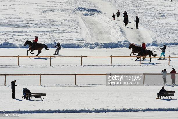 People practice skijoring on the frozen surface of the Lake St Moritz on a sunny winter day on February 25 2017 / AFP / Michael Buholzer