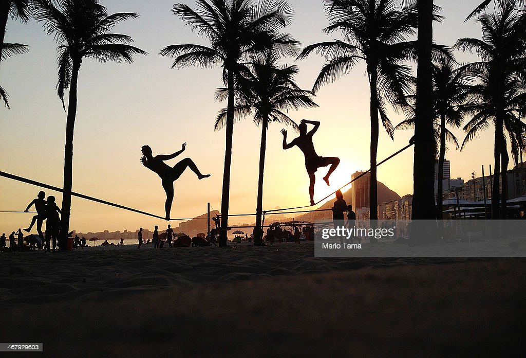 People practice slacklining on Copacabana Beach on February 8, 2014 in Rio de Janeiro, Brazil. Brazil is ramping up to host the 2014 FIFA World Cup and 2016 Olympic Games.