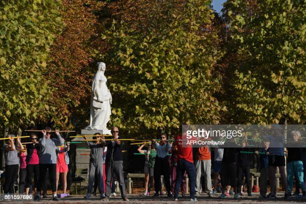 People practice stretching at the Jardin du Luxembourg in Paris on October 15 2017 during unusually warm autumnal temperatures / AFP PHOTO /...