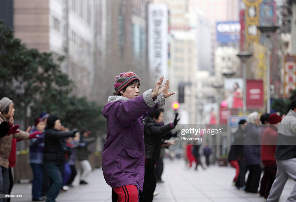 People practice Tai Chi in the East Nanjing Road area in Shanghai, China, on Tuesday, Jan. 29, 2013. China's economic growth accelerated for the first time in two years as government efforts to revive demand drove a rebound in industrial output, retail sales and the housing market. Photographer: Tomohiro Ohsumi/Bloomberg via Getty Images