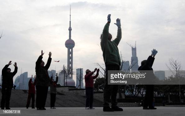People practice Tai Chi on the Bund as commercial buildings stand in the Pudong area background in Shanghai China on Tuesday Jan 29 2013 China's...