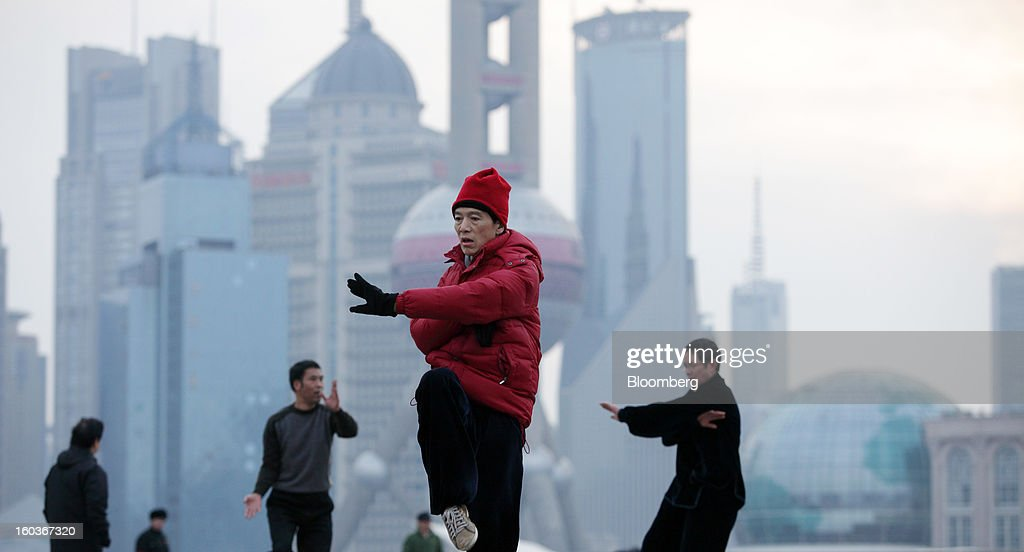 People practice Tai Chi on the Bund as commercial buildings stand in the Pudong area, background, in Shanghai, China, on Tuesday, Jan. 29, 2013. China's economic growth accelerated for the first time in two years as government efforts to revive demand drove a rebound in industrial output, retail sales and the housing market. Photographer: Tomohiro Ohsumi/Bloomberg via Getty Images