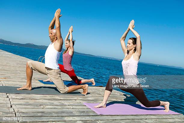 People practicing yoga on a boardwalk, horse rider pose