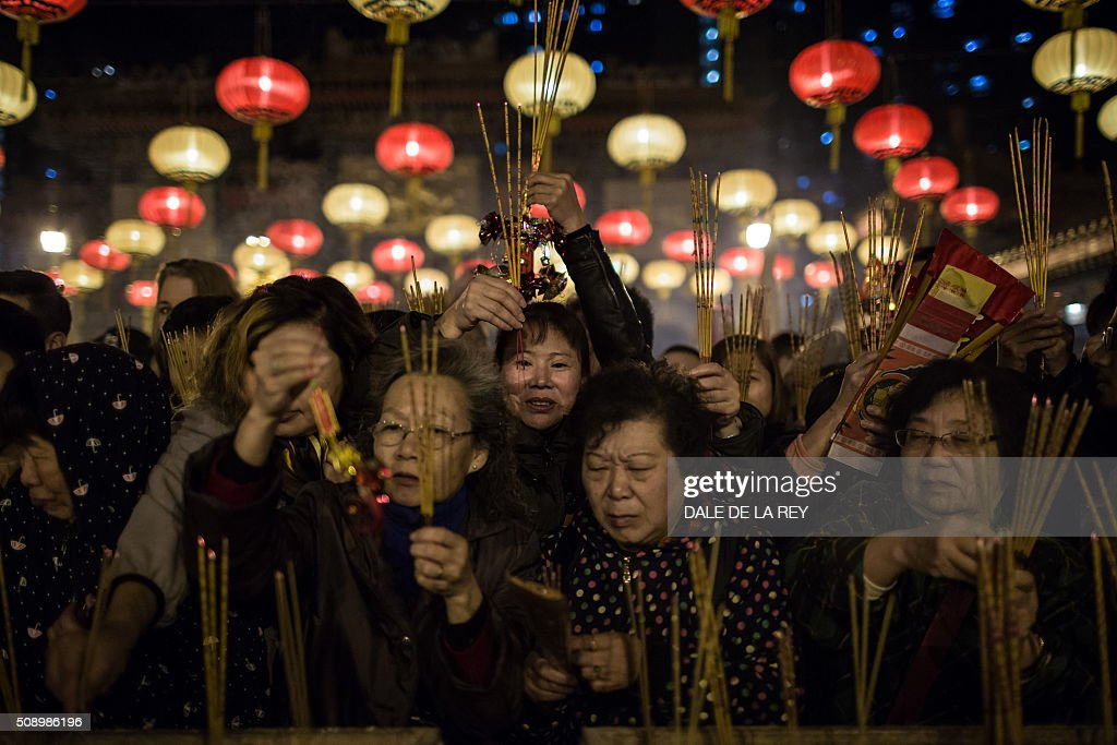 People pray and burn joss sticks at Wong Tai Sin temple to welcome in the Lunar New Year in Hong Kong early on February 8, 2016. The Lunar New Year of the Monkey begins on February 8. AFP PHOTO / DALE DE LA REY / AFP / DALE de la REY