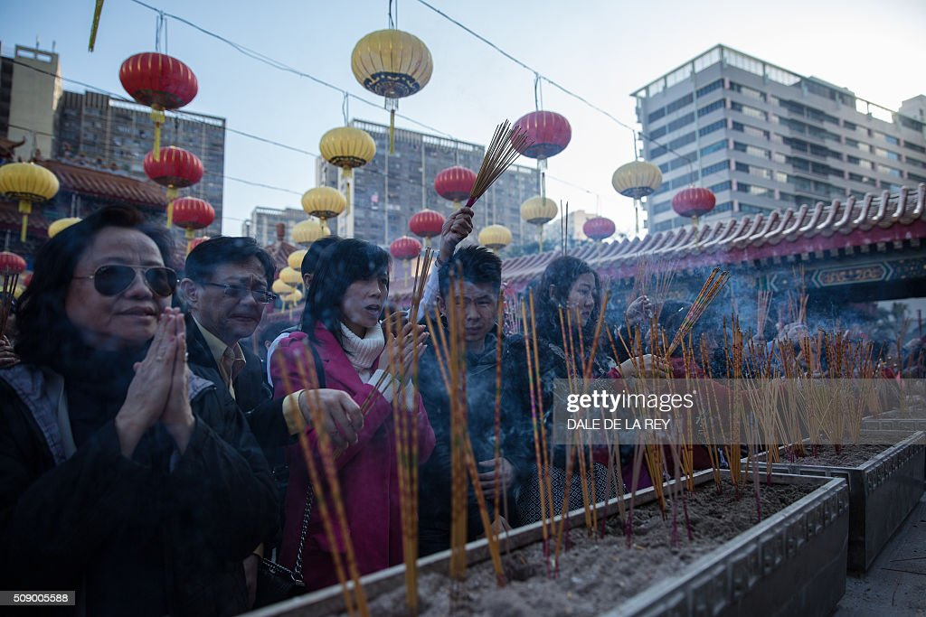 People pray and burn joss sticks at Wong Tai Sin temple to welcome in the Lunar New Year in Hong Kong on February 8, 2016. The Lunar New Year of the Monkey begins on February 8. AFP PHOTO / DALE DE LA REY / AFP / DALE de la REY